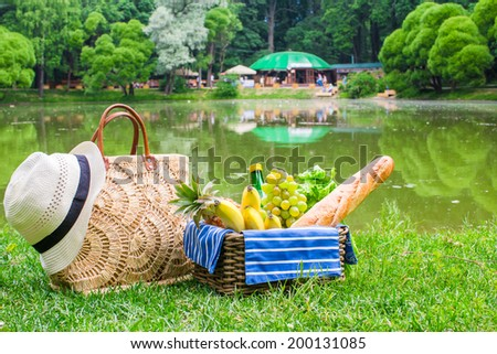Picnic basket with fruits, bread and hat on straw bag - stock photo