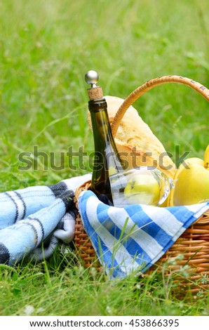 Picnic basket with fruits wine and bread on the grass with blanket aside