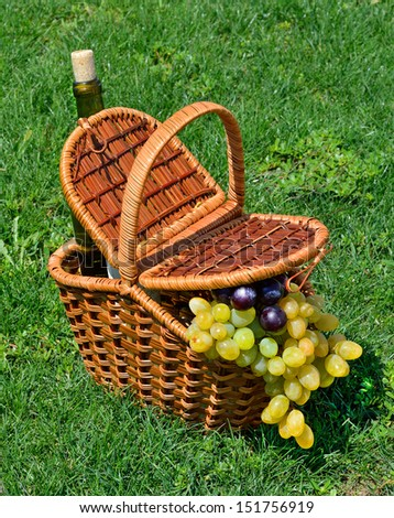 picnic basket with h ripe grape, bottle of wine on the green grass - stock photo