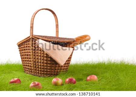 Picnic basket with long loaf and apples on the grass. Objects are isolated on white.