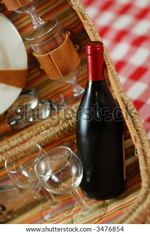 Picnic basket with wine and glasses on classic cloth - stock photo