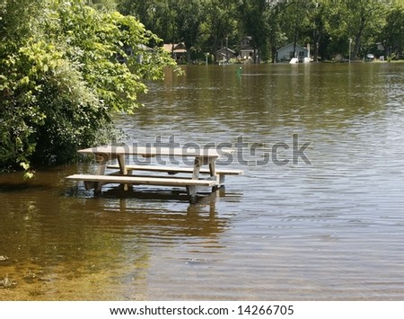 Picnic bench in flooded park - stock photo