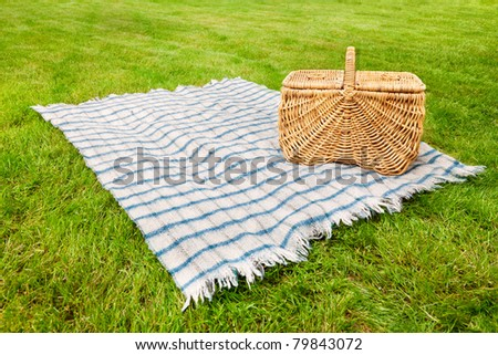Picnic blanket and basket in the grass - stock photo