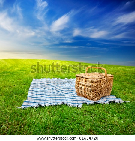 Picnic blanket and basket in the grass with dramatic twilight sky - stock photo
