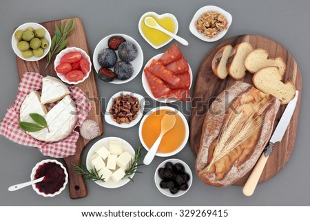 Picnic food still life with meat, cheese, fruit, vegetables, jam, honey and herbs with rustic french bread loaf on maple boards. - stock photo