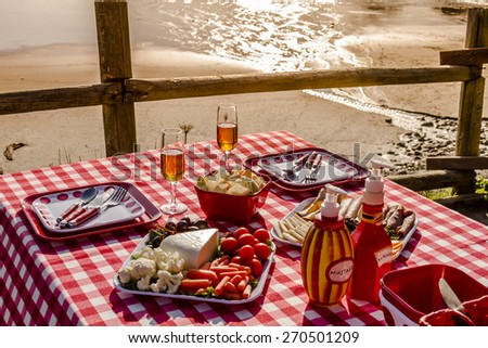 Picnic for 2 at the beach overlooking the ocean with haystack rocks at sunset with table set with food, dishes, wine glasses filled with wine and red checkered table cloth - stock photo