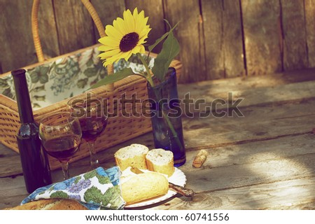 Picnic for two with wine, bread and cheese. - stock photo