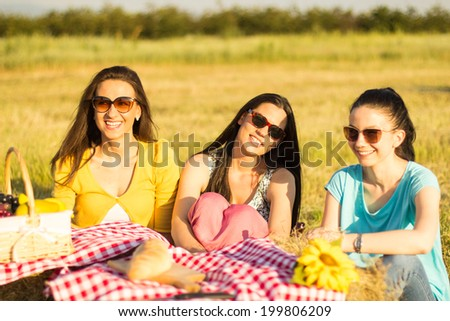 Picnic fun. Three girls having fun at a picnic in the countryside - stock photo