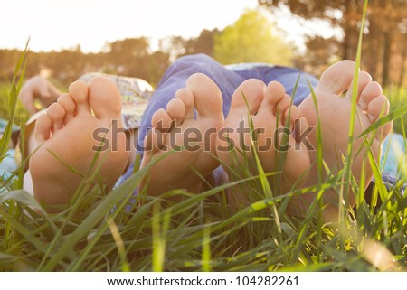 picnic, male and female feet on the green grass - stock photo