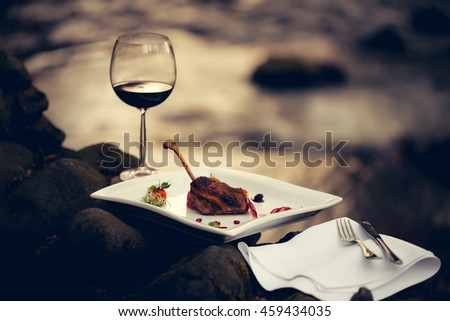 Picnic near water, decorated meat with lemon, glass of wine, served food