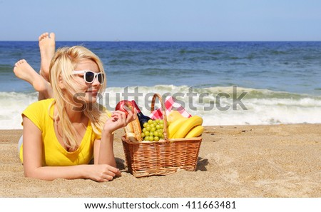 Picnic on the Beach. Blonde Young Woman with Basket of Food on the Shore
