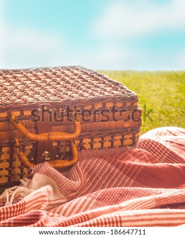 Picnic rug and wicker hamper standing on a green field under a blue sky on a hot summer day for a healthy outdoor lifestyle, closeup in warm sunshine - stock photo