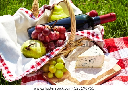 Picnic setting with wine, blue cheese, pears and grapes - stock photo