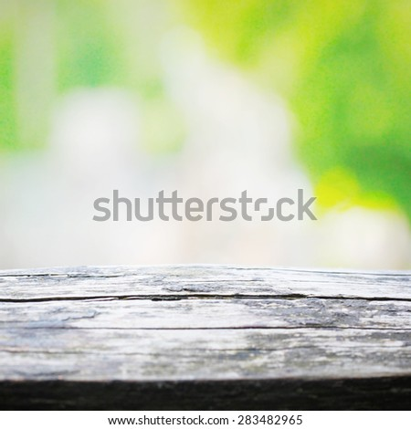 Picnic table in natural bokeh background - stock photo
