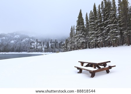 Picnic table in the snow at Mammoth Lakes, Sierra Nevada, California - stock photo