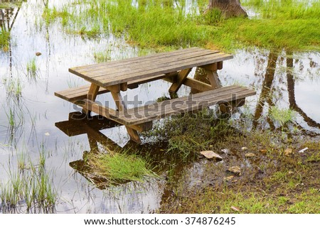 Picnic table isolated in a flooded campground - stock photo