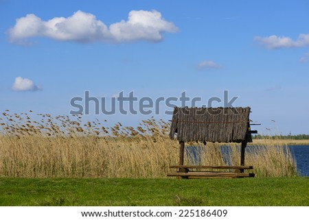 Picnic table on a summer day with a bright blue cloudy sky, reed, lake and green field background - stock photo