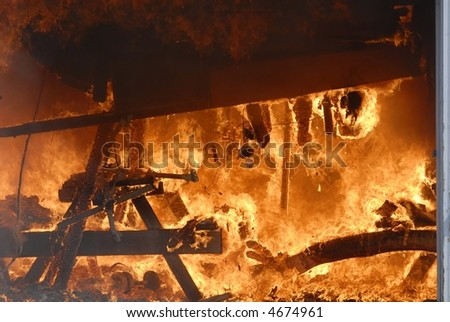 picnic table on fire with roof falling - stock photo