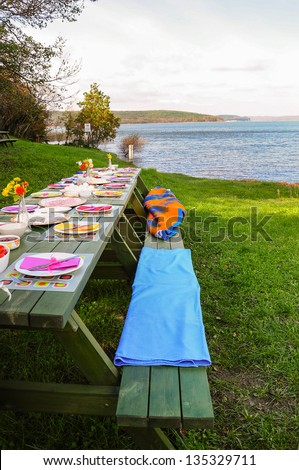 picnic table on grass by lake - stock photo