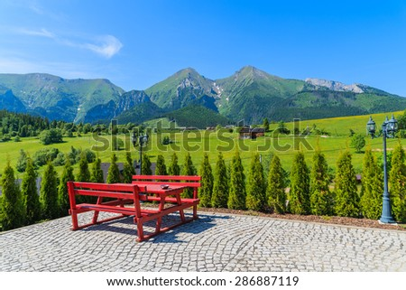 Picnic table on Zdiar village with view of Tatry Bielskie Mountains in summer, Slovakia - stock photo