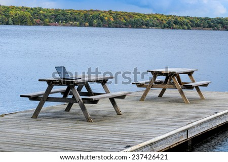 Picnic table with a computer at a lake - stock photo