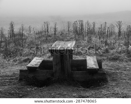 Picnic table with benches in autumn misty weather, black and white image - stock photo