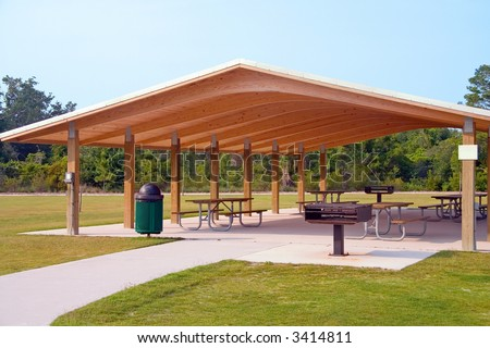Picnic tables and grill under wood roof structure in local park - stock photo