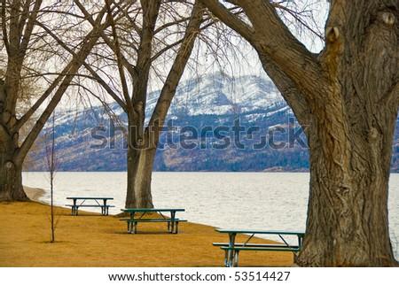 Picnic tables at the beach of Okanagan Lake, Kelowna, Canada. - stock photo