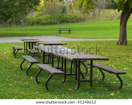 Picnic tables in autumn - stock photo