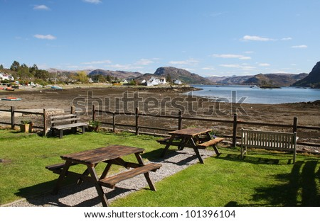 Picnic tables with the village of Plockton and Loch Carron in the background