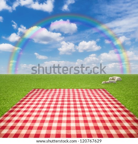 Picnic template with tablecloth in grass field and rainbow in sky - stock photo