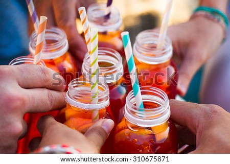 Picnic theme: group of friends holding drinks, toast , close-up - stock photo