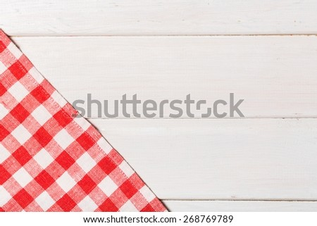 Picnic. White and red tablecloth textile texture on wooden table background - stock photo