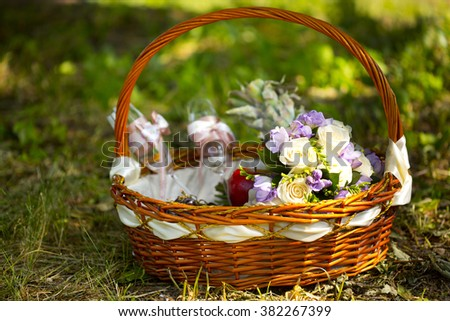 Picnic wicker basket with wedding bouquet of white and violet flowers and two glasses of champagne