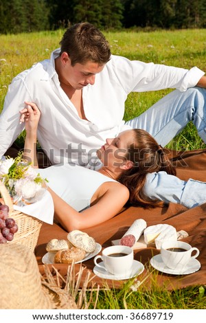 Picnic - Young couple in spring meadow