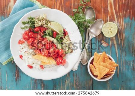 Pico de Gallo, fresh Mexican salsa. Pico de gallo and nacho chips on rustic wooden table background. Natural light - stock photo