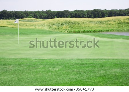 pictire of golf landscape with green grass and stream