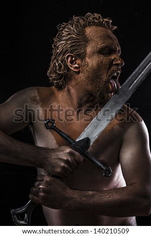 Pictish warrior licking a sword, covered in mud and naked - stock photo