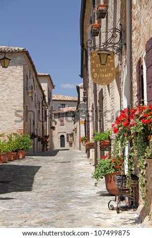 pictorial narrow paved street in village Montegridolfo in province of Rimini, Emilia Romagna, Italy, Europe - stock photo