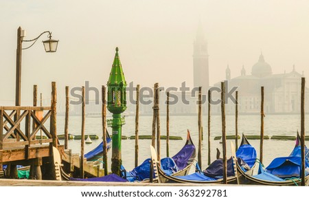 Pictorial view of blue gondolas in Venice, Italy, with ancient green lantern in the front - stock photo