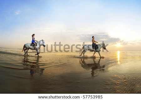 Picture a couple in love, which is galloping on a horse of the sea at sunset - stock photo