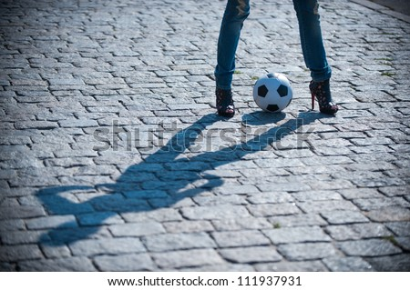 Picture a pair of shapely female legs with a football - stock photo