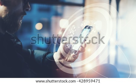 Picture businessman relaxing modern loft office.Man sitting in chair at night.Using contemporary smartphone,blurred background. Digital Connections World Wide Interfaces.Horizontal,film effect - stock photo