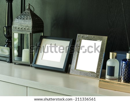 Picture frame and candle lamp on a table in a contemporary room - stock photo