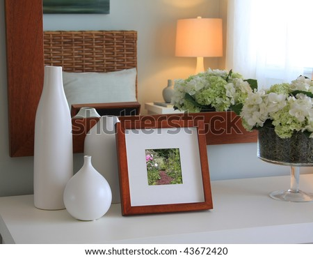 Picture frame and flowers on a dresser in a contemporary bedroom. (Picture in frame is mine.) - stock photo