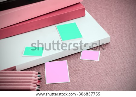 Picture frame and pile of books on wooden table. - stock photo