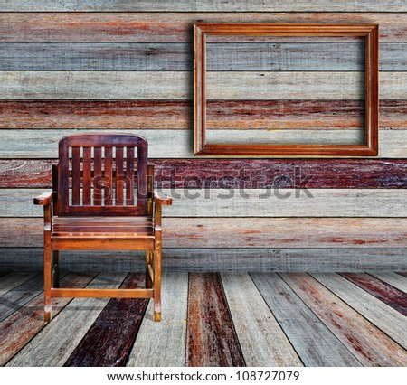 Picture frame and wood chair in grunge room. - stock photo
