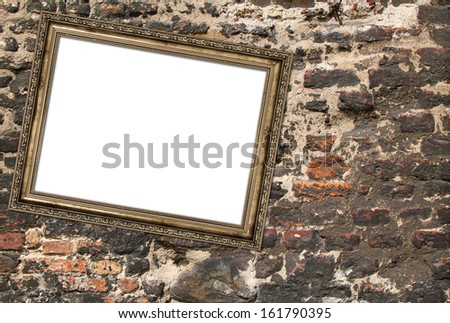 picture frame crookedly hung over ruined brick wall - stock photo