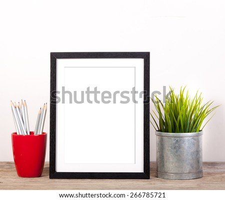 picture frame with office items and pot plant on wooden table