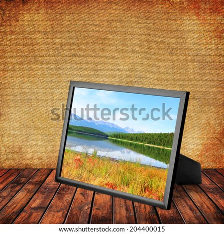 Picture frame with Rocky Mountains lake and blossoming pink herbs ashore in Jasper National Park (Alberta. Canada) on the wooden textured background. Collage of my photos  - stock photo